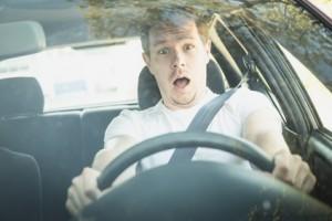 Junger Mann sitzt im Auto und ist schockiert